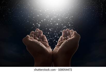 Star falling from the dark night sky to hands