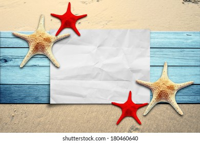 Star fish and paper on wooden floor and sand