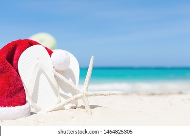 Star fish with Santa claus hat on sandy beach close to sea. Tourism and christmas vacation concept background