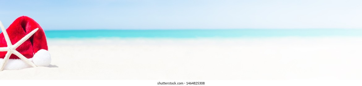 Star fish with Santa claus hat on sandy beach close to sea. Tourism and christmas vacation concept background with copy space,  long banner