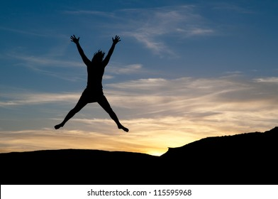Star jump for joy at sunset. Young woman in the air as a silhouette figure.