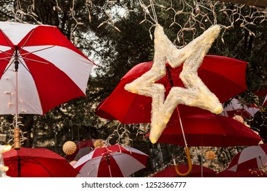Star with luminous lights on the background of umbrellas hanging from tree branches