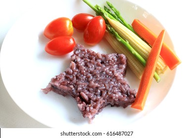 Star shape brown rice with tomato, baby corn ,asparagus  in white plate.