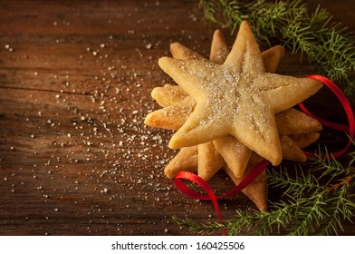 Star shaped christmas cookies, pine tree branch and red ribbon on vintage wood background - dark moody image.
