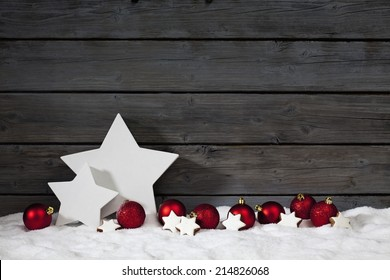 Star shaped christmas decoration christmas bulbs cinnamon stars on pile of snow against wooden wall