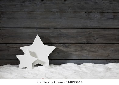 Star shaped christmas decoration on pile of snow against wooden wall