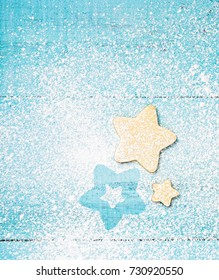 Star shaped Christmas Linzer cookies with icing sugar on a blue background.