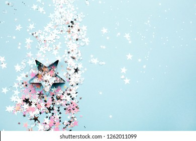 Star shaped form with holographic and silver glitter on blue pastel background. Festive concept. Place for text.