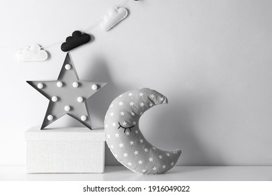 Star shaped lamp, toy moon and box on table, space for text. Interior design