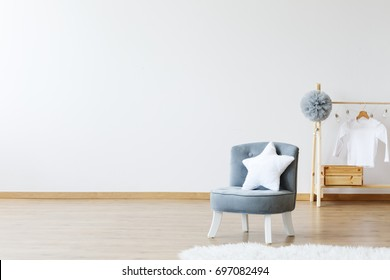 Star shaped pillow on a grey chic chair in a minimalist design scandinavian room