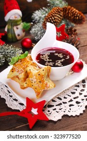 star shaped puff pastries with mushrooms and cup of red borscht for christmas eve on wooden table