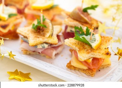 Star shaped toasts with smoked salmon, meat  and cheese.