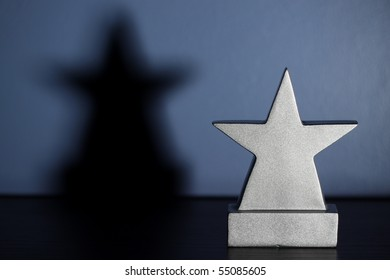 Star shaped trophy and shadow, sitting in a boys blue bedroom awaiting your engraving.