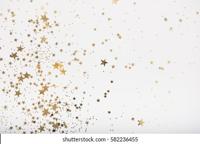 Star Shaped Various Size Golden Glitter Bits on White Background