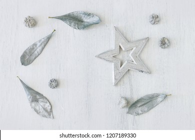 Star and silver leaves on white wooden background. Top view, Christmas motif.