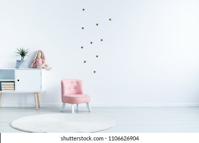 Star stickers on white wall with copy space in child's room interior with pink chair. Real photo