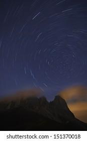 Star tracks over Sassolungo mountain range. Dolomites mountains, Italy