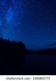 Star tracks upon top of trees and lake. Starry night sky in cloudy weather. Kenozersky National Park, Arkhangelsk region, Russia.