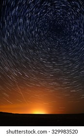 Star trail in the night sky against the backdrop of city lighting.