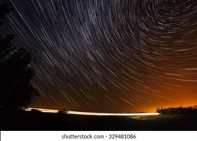 Star trail on highway illuminated light vehicles.
