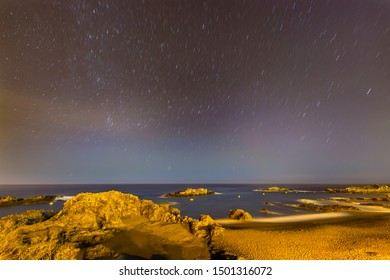 Star trails above the coastline and beach of Los Cancajos in La Palma, Spain with view to Tenerife.