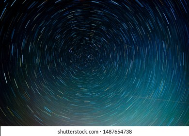 Star trails around Polaris (North Star) with comet and airplanes crossing.