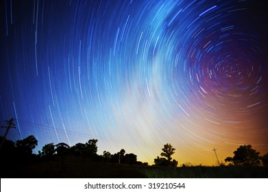 Star trails in a colorful night sky with the silhouette of the horizon in the foreground.