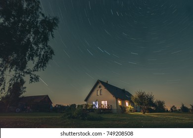 Star trails at night at farm in countryside. Night atmosphere at farm with surrounding technique.