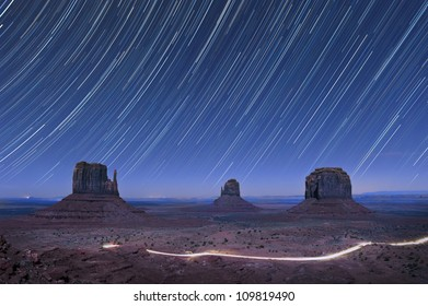 Star trails in the night over the mitten rock formations in Monument Valley, USA