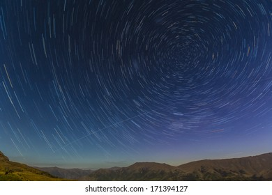 Star trails in the night sky over the Crown Range near Queenstown, New Zealand