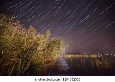 star trails over lake Balaton, falling stars or perseide on an august night - astrophotography