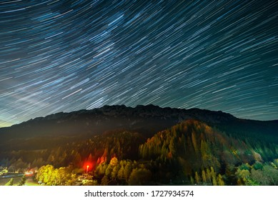 Star trails over the Plaiul Foii resort in Piatra Craiului mountains from Romania
