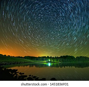 Star Trails over Seneca Lake in rural Ohio looking north toward earth's celestial pole with stars appearing to spin around Polaris, the North Star as the earth rotates.