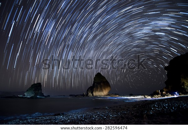 Star trails.  Stacking of long exposure images taking on a starry night to create star trails.  Location at Tanjung Papuma, East Java, Indonesia.
