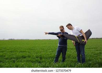 STARA PAZOVA/SERBIA - April 04, 2018: The agronomist holding field tablet computer, and the drone operator holding professional fixed wing drone, examine aerial images of crops in the wheat field