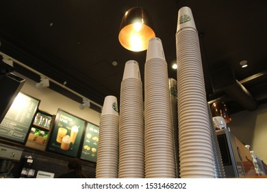 STARBUCKS COFFEE BRANCH, EDINBURGH, SCOTLAND - 15 October 2019 Stacks of Single Use Disposable Take Away Coffee Cups at Starbucks Coffee