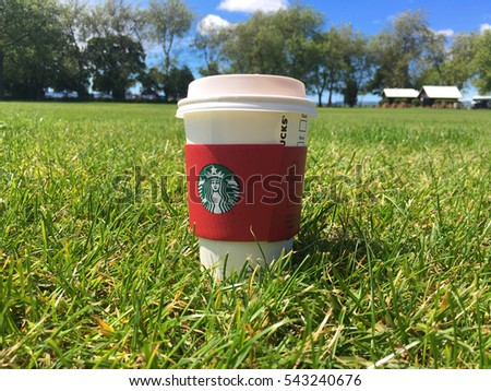 A Starbucks Latte on Green Grass Park. Starbucks is the world's largest coffee house with over 20,000 stores in 61 countries.