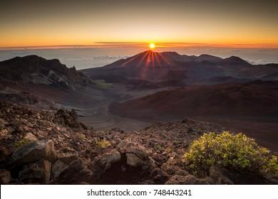Starburst sunrise shot on the summit of Haleakala Volcano overlooking the volcanic crater  in Haleakala National Park on Maui in Hawaii