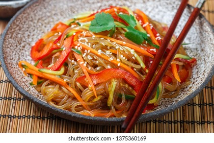 Starch (rice, potato) noodles with vegetables - bell peppers, carrots, cucumber, sesame seeds, cilantro and soy sauce. Vegetarian dish. A delicious lunch or dinner in the Asian style. Cold (hot) salad