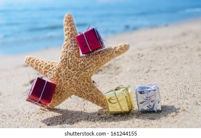 Starfish with few Christmas gift box on the sandy beach by the ocean