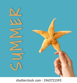 Starfish in hands of woman and lettering summer, beach relax concept. Bright summer greeting card with yellow natural seastar on sea blue colors.