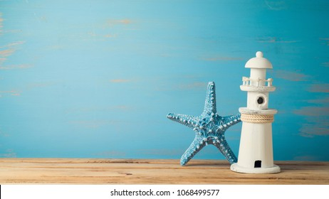 Starfish and lighthouse decor over wooden background. Summer vacation concept