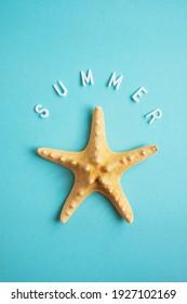Starfish auf blauem Hintergrund und das Wort Sommer. Urlaubskonzept. Vertikales Bildschirmhintergrund.