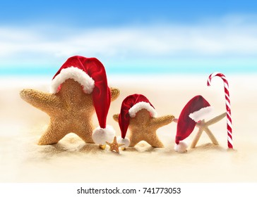 starfish in red santa hat on sandy beach and candy