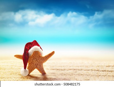 Starfish in red santa hat at the seaside. Christmas in summer.
