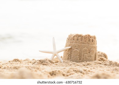Starfish and sandcastle on the beach.