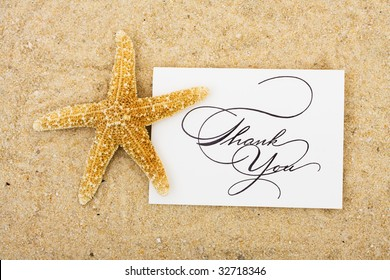 A starfish sitting on a thank you card with a sand background, turtle