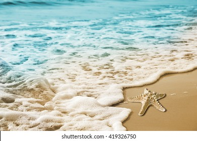 Starfish and soft wave on the sandy beach summer tropical concept