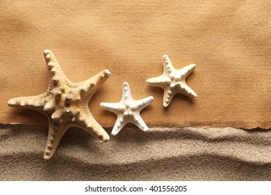 Starfishes and handmade paper sheet on beach