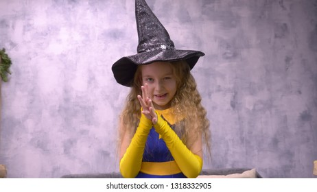 Stargazer girl rubs hands. Close up front view little witch viciously rubs her hands, ready to cast a spell wizard Helloween hat. Wish warlock close up front view
